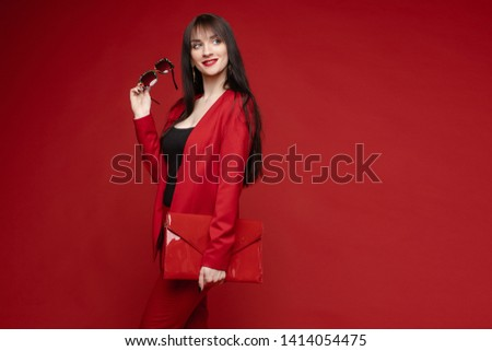 Side view of glamorous brunette posing in red smart suit #1414054475