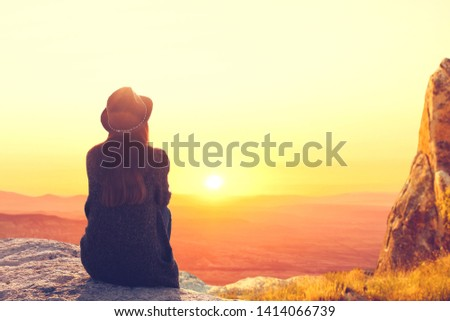 A woman sits on top of a mountain and admires the beautiful natural landscape. Digital detox and soul search. Unplugged #1414066739