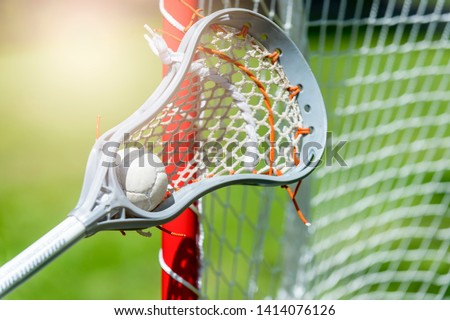 Abstract view of a lacrosse stick scooping up a ball. Sunny day
