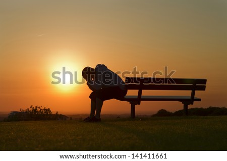 Portrait of a Sad or unhappy man sitting on a bench at Sunset Royalty-Free Stock Photo #141411661