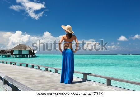 Woman on a tropical beach jetty at Maldives #141417316