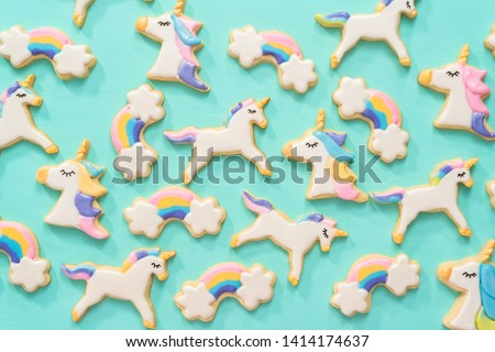 Flat lay. Unicorn sugar cookies decorated with royal icing and food glitter on a blue background.
