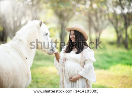 A beautiful young pregnant asian woman wearing a cowboy hat is feeding a white horse in the park.