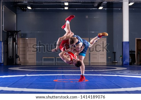 The concept of fair wrestling. Two greco-roman  wrestlers in red and blue uniform wrestling   on a wrestling carpet in the gym.The concept of fair wrestling