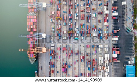 aerial top view of logistics import and export  transportation of Container Cargo ship with working crane bridge in shipyard at the port, industrial context #1414190909