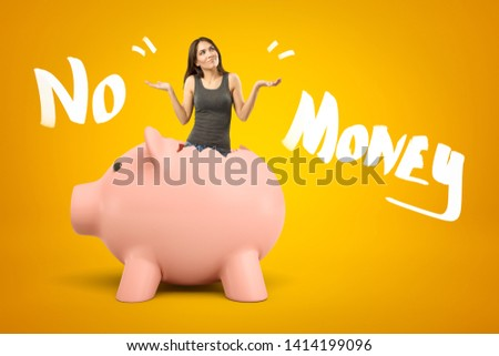 Young brunette girl wearing casual jeans and t-shirt appearing out of broken piggy bank with NO MONEY sign on yellow background. Banking and finance. Money and savings. Gestures and body language. #1414199096