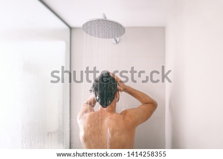 Man taking a shower washing hair with shampoo product under water falling from luxury rain shower head. Morning routine luxury hotel lifestyle guy showering. body care hygiene. #1414258355