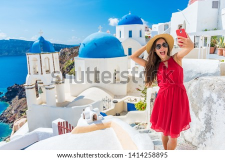 Santorini tourist girl on cruise holiday taking selfie photo with phone at famous three domes church, European tourism attraction in Greece. Asian woman on vacation. #1414258895