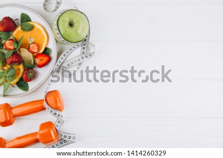 Diet plan, menu or program, tape measure, water, dumbbells and diet food of fresh fruits on white background, weight loss and detox concept, top view #1414260329