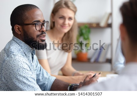 Excited male african-american talking to coworkers timeout in office informal partners conversation. Black manager telling interesting story, sharing news, business strategy. Blur background #1414301507