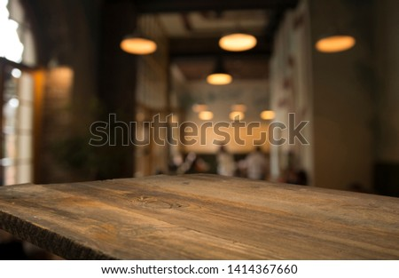 image of wooden table in front of abstract blurred background of resturant lights #1414367660