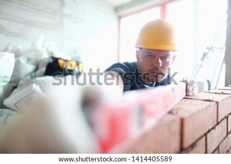 Portrait of skilled professional bricklayer using special equipment and tools to measure balance and height of brick wall. Prudent builder wearing hard gloves to keep hands unharmed. Building concept #1414405589