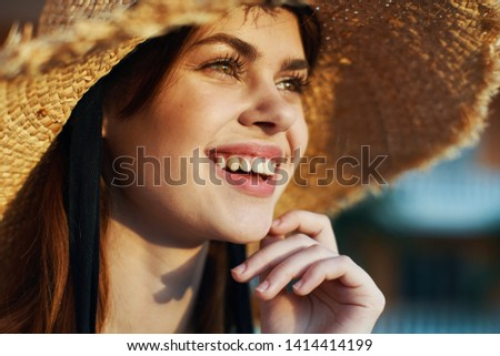 happy woman in a straw hat looks away and laughs close-up                     #1414414199