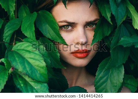 Confident look beautiful woman bright makeup close-up green leaves park                 #1414414265