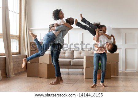 Happy african american family with cute children having fun embracing lifting laughing standing among boxes, funny mixed race parents and kids celebrate moving day relocation renovation in new house #1414416155