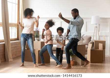 Happy african american parents and cute children dancing among boxes celebrating moving day relocation renovation, active carefree funny mixed race family mom dad having fun with kids in new house #1414416173