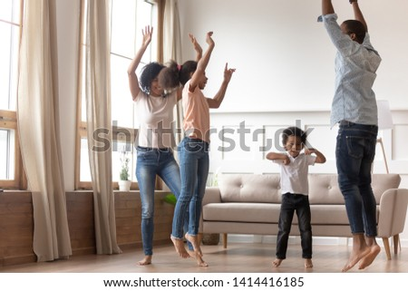 Joyful happy african family having fun jumping in living room together, active black parents and little cute kids dancing at home, mixed race mom dad with small kids laughing enjoy leisure activity #1414416185