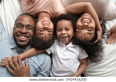 Happy mixed race family of four lying on bed cuddling, smiling african american dad mom and little kids bonding looking at camera, loving black parents children unity connection, portrait, top view #1414416200