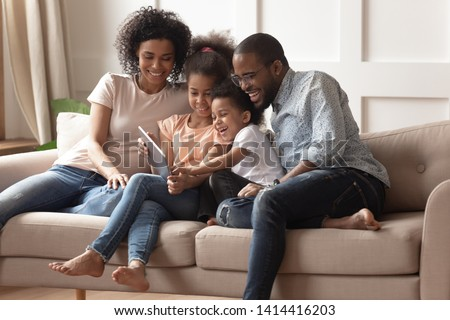 Happy african family having fun with device at home, black parents and little children using digital tablet looking at screen sit on sofa together, cute kids hold computer laugh watch cartoons online #1414416203