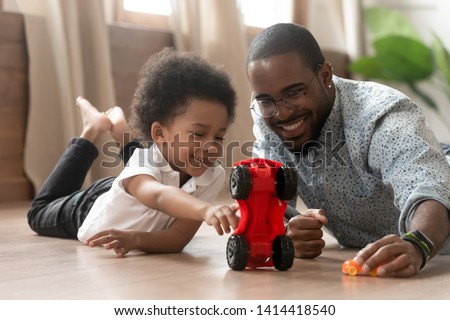 Cute little african kid son play toy cars with black dad, happy family small mixed race son and loving young father babysitter having fun racing on warm floor at home, family daddy child leisure game #1414418540