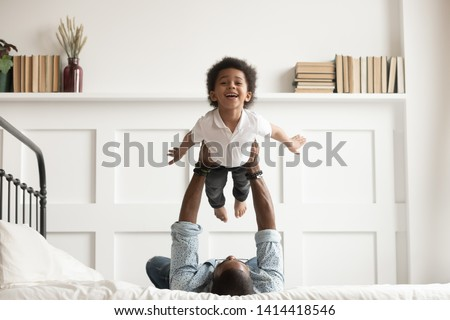 Happy funny african american kid boy flying in fathers arms looking at camera in bedroom, loving family single black dad holding lifting cute little child son playing plane bonding having fun on bed