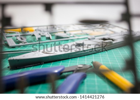 Building plastic model WW2 battleship with part and tools on cutting pad closeup. #1414421276