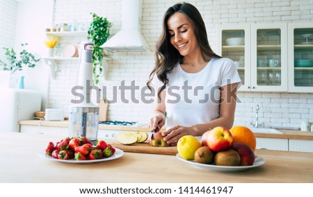Beautiful woman making fruits smoothies with blender. Healthy eating lifestyle concept portrait of beautiful young woman preparing drink with bananas, strawberry and kiwi at home in kitchen. #1414461947