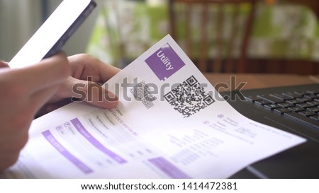 QR Code Payment. Utility Billing Online. Payment of utilities using QR code and mobile device. A man scanning the QR code with app and paying utility bills using his smartphone Royalty-Free Stock Photo #1414472381