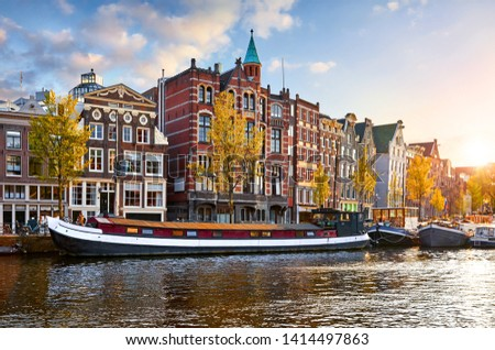 Amsterdam, Netherlands. Floating Houses and houseboats and boats at channels by banks. Traditional dutch dancing houses among trees. Evening autumn street above water pink sunset sky with clouds. #1414497863