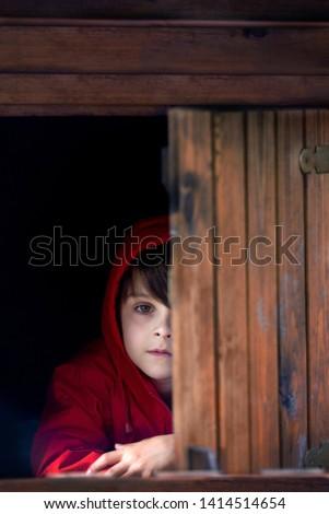 Preteen boy in red sweatshirt, hiding behind a wooden door, looking scared and sad #1414514654