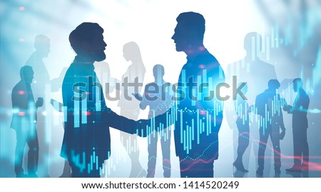 Silhouettes of business people shaking hands and talking over blurred background with double exposure of forex graphs. Concept of trading and teamwork. Toned image #1414520249