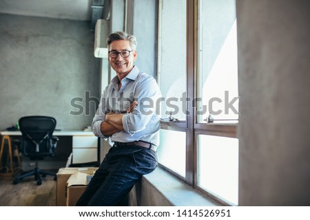 Smiling businessman looking at camera as he stands by a window sill with arms crossed. Mid adult businessman at his office. #1414526951