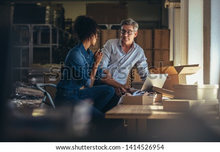 Two business partners working together at warehouse for online seller business. People discussing while preparing the package to delivery. #1414526954