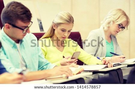education, high school, university, learning and people concept - student girl with smartphone at lecture #1414578857