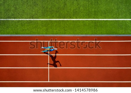 Amazing girl in a blue sportswear and sneakers runs on the running track at the stadium outdoors. Sun shines onto her body. Top view aerial photo. Horizontal. #1414578986