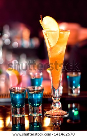 blue, strong alcoholic drink in small glasses and an appletini on bar waiting to be served #141462670
