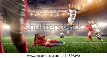 Female Soccer players performs an action play on a professional soccer stadium. Girls playing soccer #1414629890