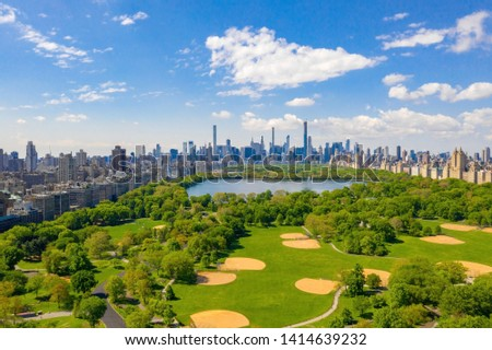 Aerial view of the Central park in New York with golf fields and tall skyscrapers surrounding the park. #1414639232