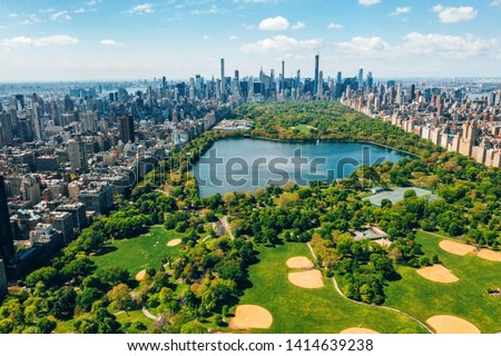 Aerial view of the Central park in New York with golf fields and tall skyscrapers surrounding the park. #1414639238