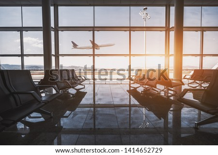 Wide-angle view of a modern aircraft gaining the altitude outside the glass window facade of a contemporary waiting hall with multiple rows of seats and reflections indoors of an airport terminal #1414652729