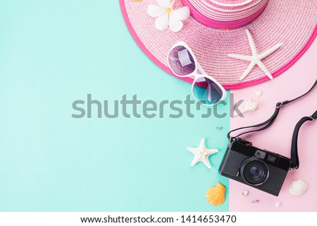 Top view of Beach accessories Picture Frame, sunglasses, starfish beach hat and sea shell on bright pastel green background for summer holiday and vacation concept. Flat lay.