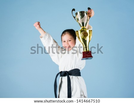 small girl with champion cup. martial arts. winner little girl in gi sportswear. practicing Kung Fu. childhood. knockout. energy and activity for kids. sport success in single combat. Sporty beauty. #1414667510