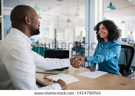 Smiling African American manager sitting at his desk in an office shaking hands with a job applicant after an interview #1414700966