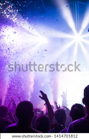 Stage lights and crowd of audience with hands raised at a music festival. Fans enjoying the party vibes. #1414701812