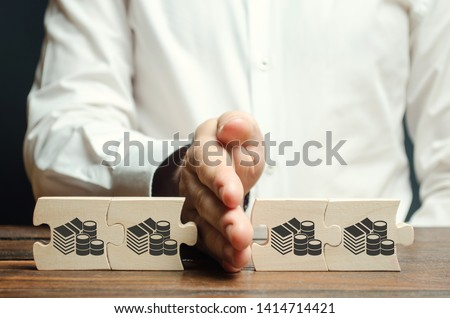 Businessman separates the wooden puzzle with a picture of money. The concept of financial management and distribution of funds. Saving and investing. Property division. Divorce and legal services Royalty-Free Stock Photo #1414714421