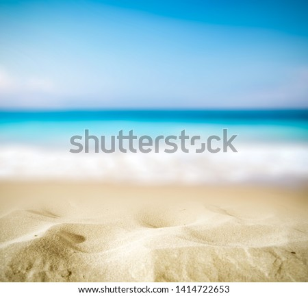 Summer background of hot sand with free space for your decoration and blurred background of ocean with summer sun light.  #1414722653