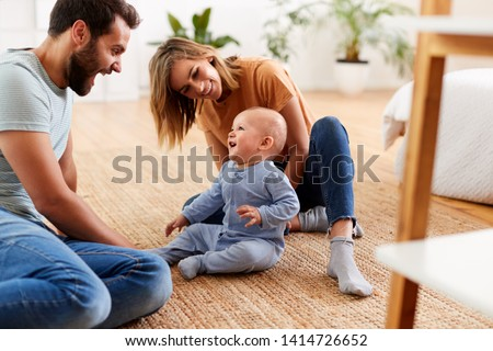 Parents Sitting On Floor At Home Playing With Baby Son #1414726652