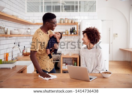 Multi-Tasking Father Holds Baby Son And Cleans Surface As Mother Uses Laptop And Eats Breakfast #1414736438