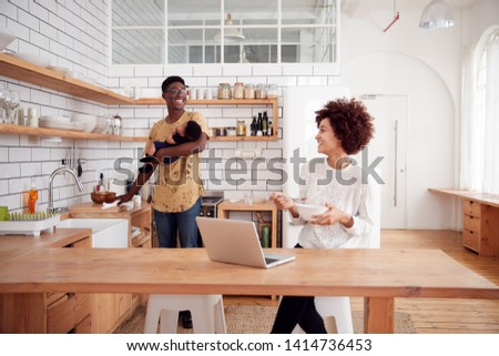 Multi-Tasking Father Holds Baby Son And Cleans Surface As Mother Uses Laptop And Eats Breakfast #1414736453