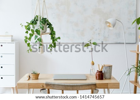 Stylish and boho home interior of open work space with wooden desk, chair, lamp, laptop and white shelf. Design and elegant personal accessories. Botany and minimalistic home decor with plants. #1414745657